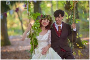 bride with flowers in her hair and red doc martins sits on swing with groom at dusk at an outdoor wedding in sussex