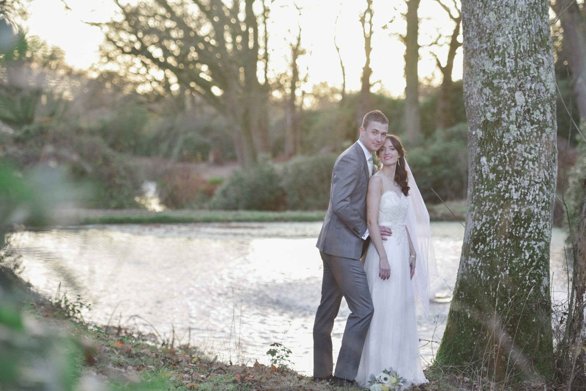 bride and groom embracing by a lake at south lodge sussex