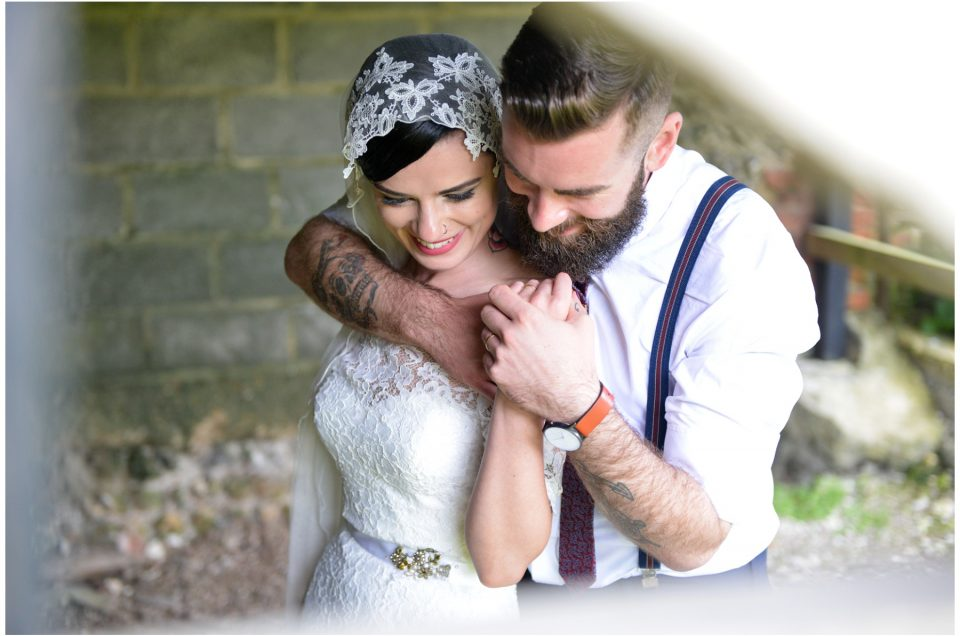 Tattooed bride and groom in an embrace