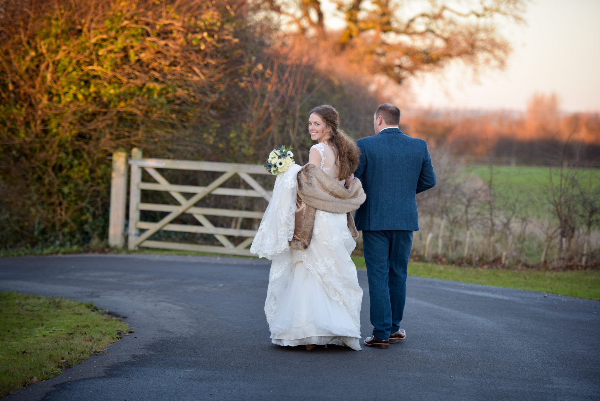 bride and groom walking away towards autumn sunset as bride turns to look at camera