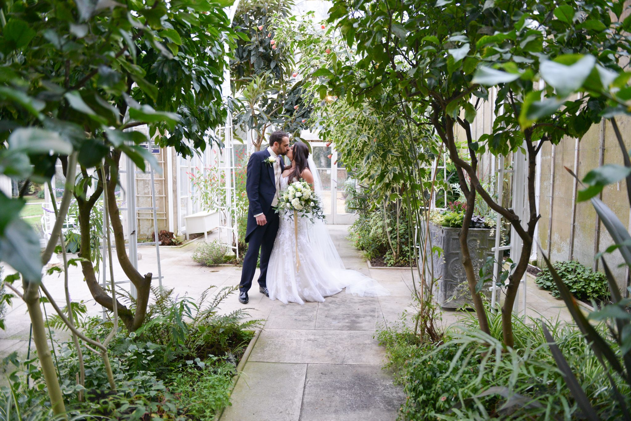 bride and groom kissing in conservatory at wiston house sussex