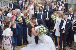 happy wedding couple kissing with wedding guests at wiston house in sussex