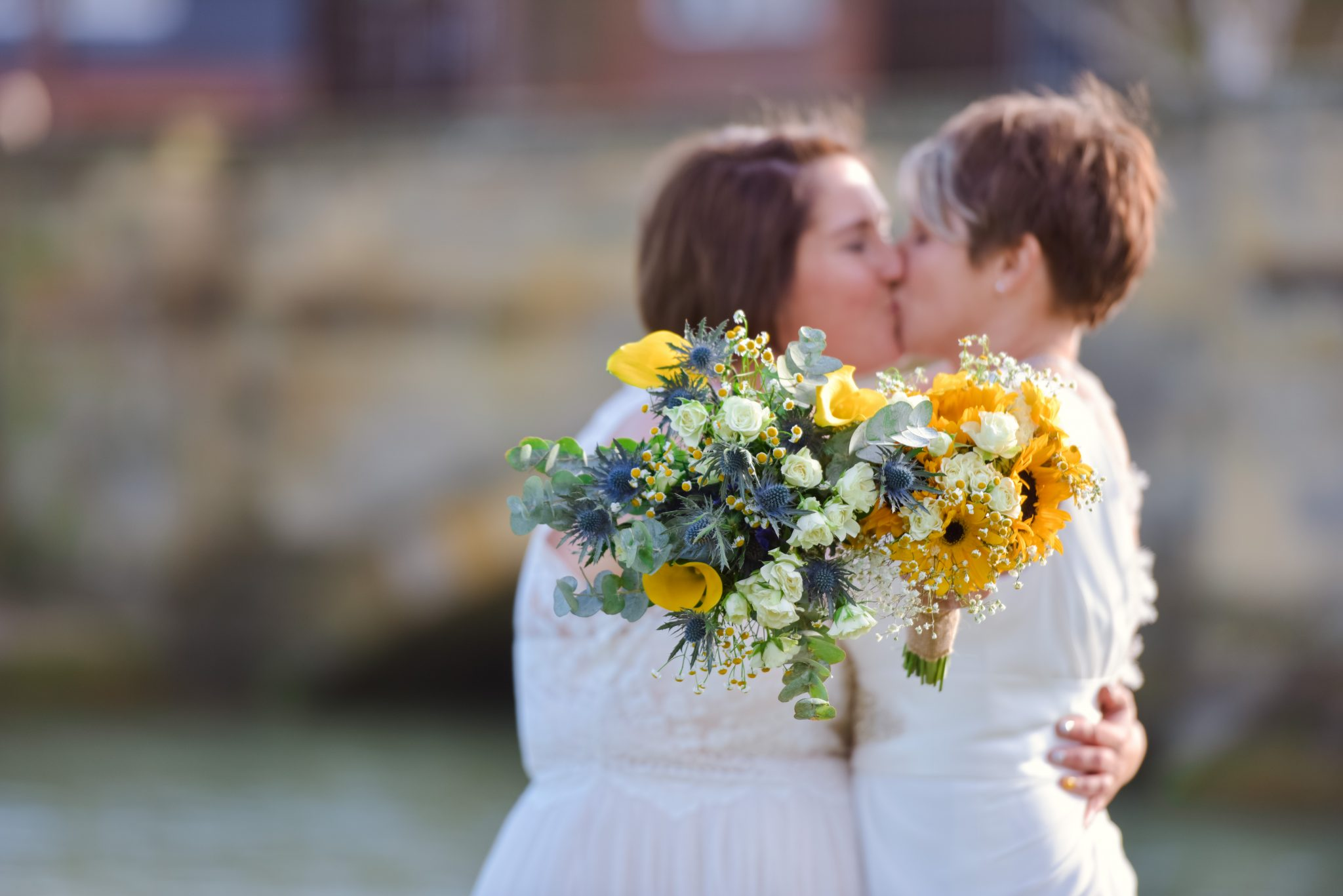 two brides kissing by a river with their yellow boquets