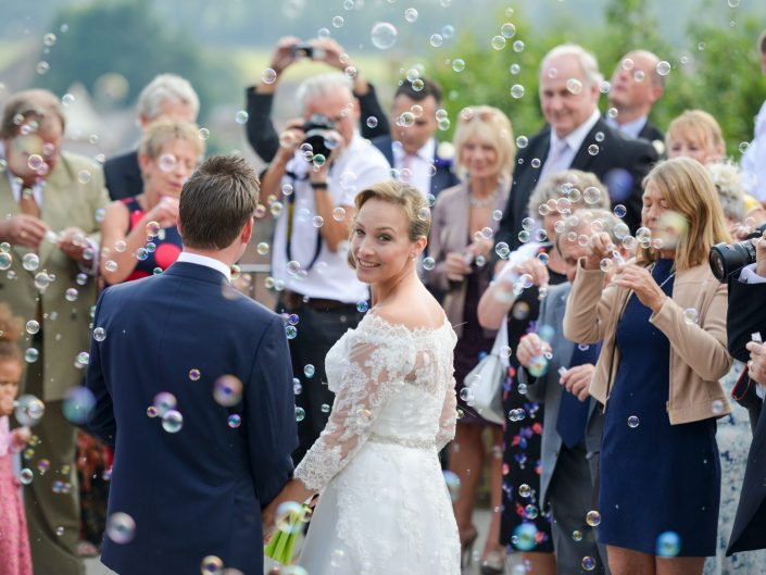 wedding bubbles with bride looking back at the camera over her shoulder shot at arundel town hall sussex