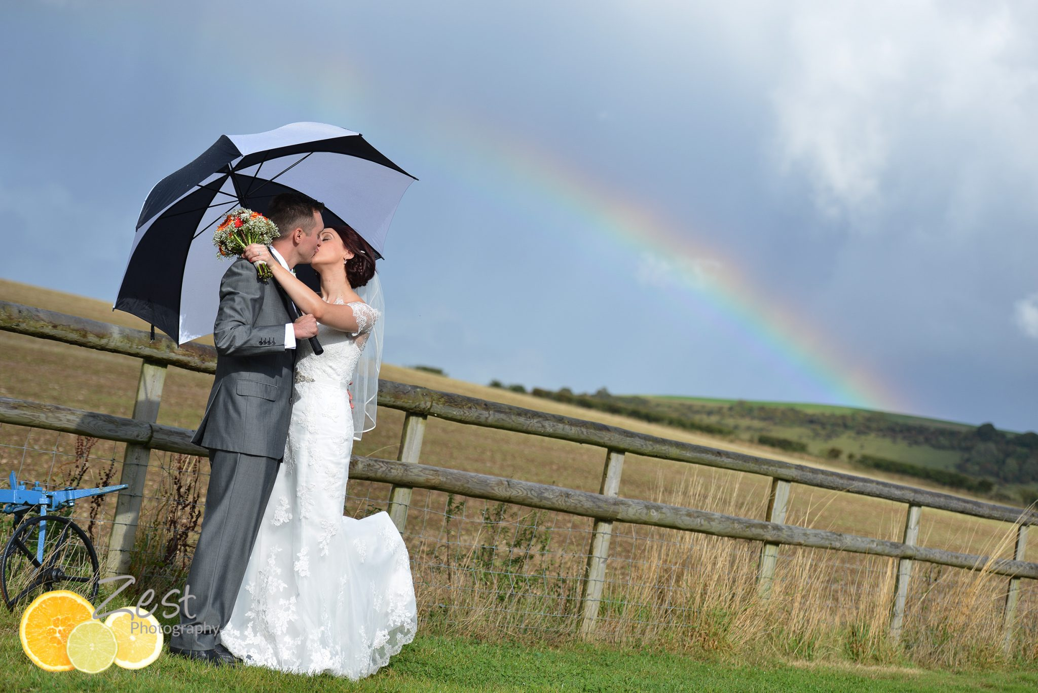 a kiss under a umbrella and rainbow at long furlong