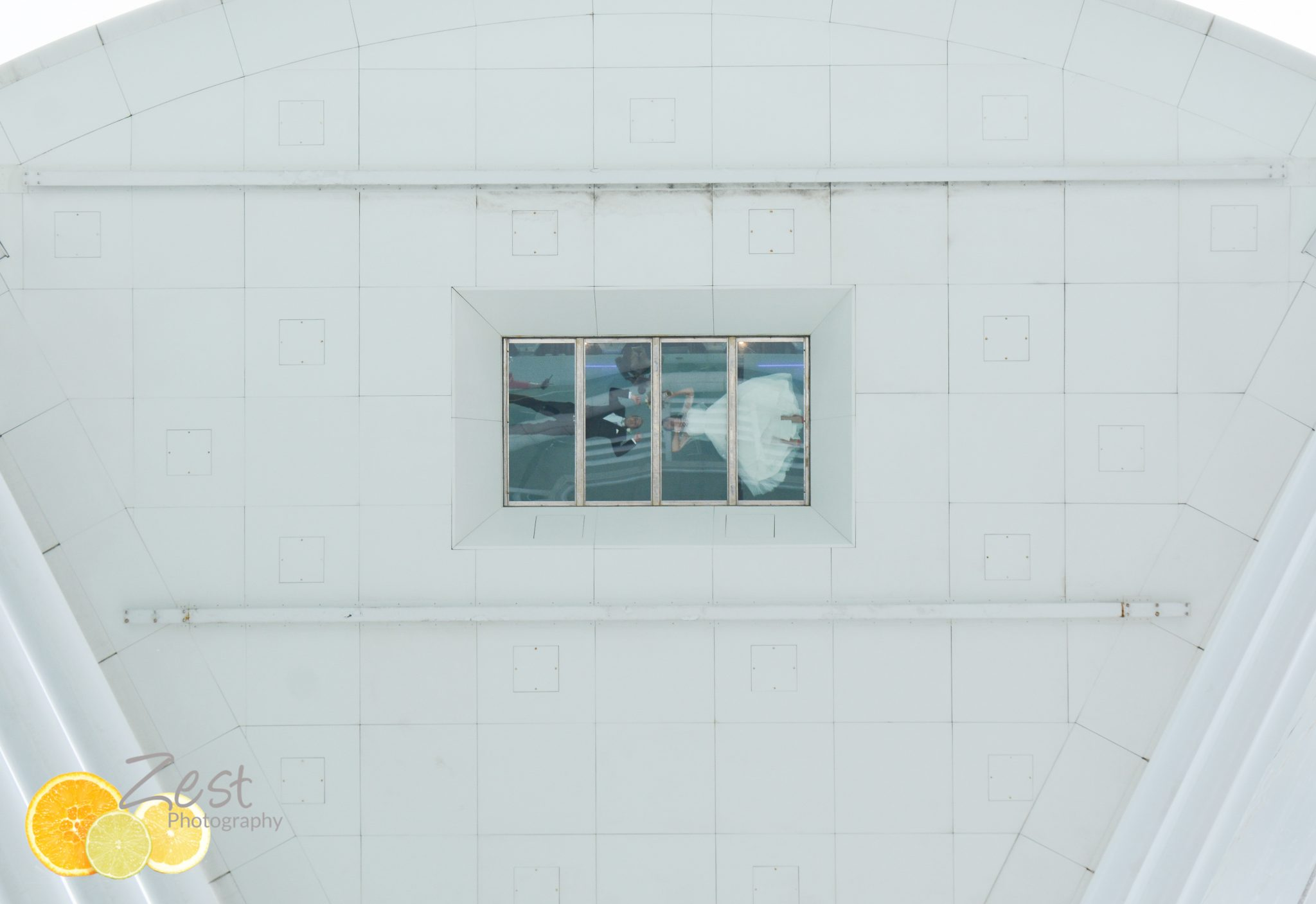 fearless wedding couple laying on the glass at spinnaker tower