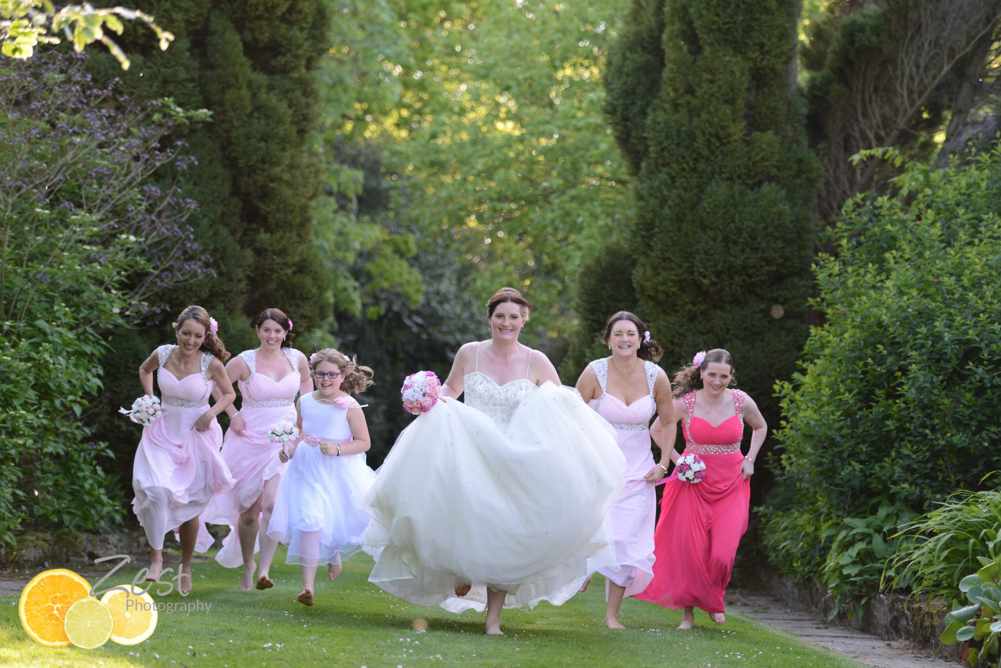 bride and brisesmaids running through the grounds at cisswood house