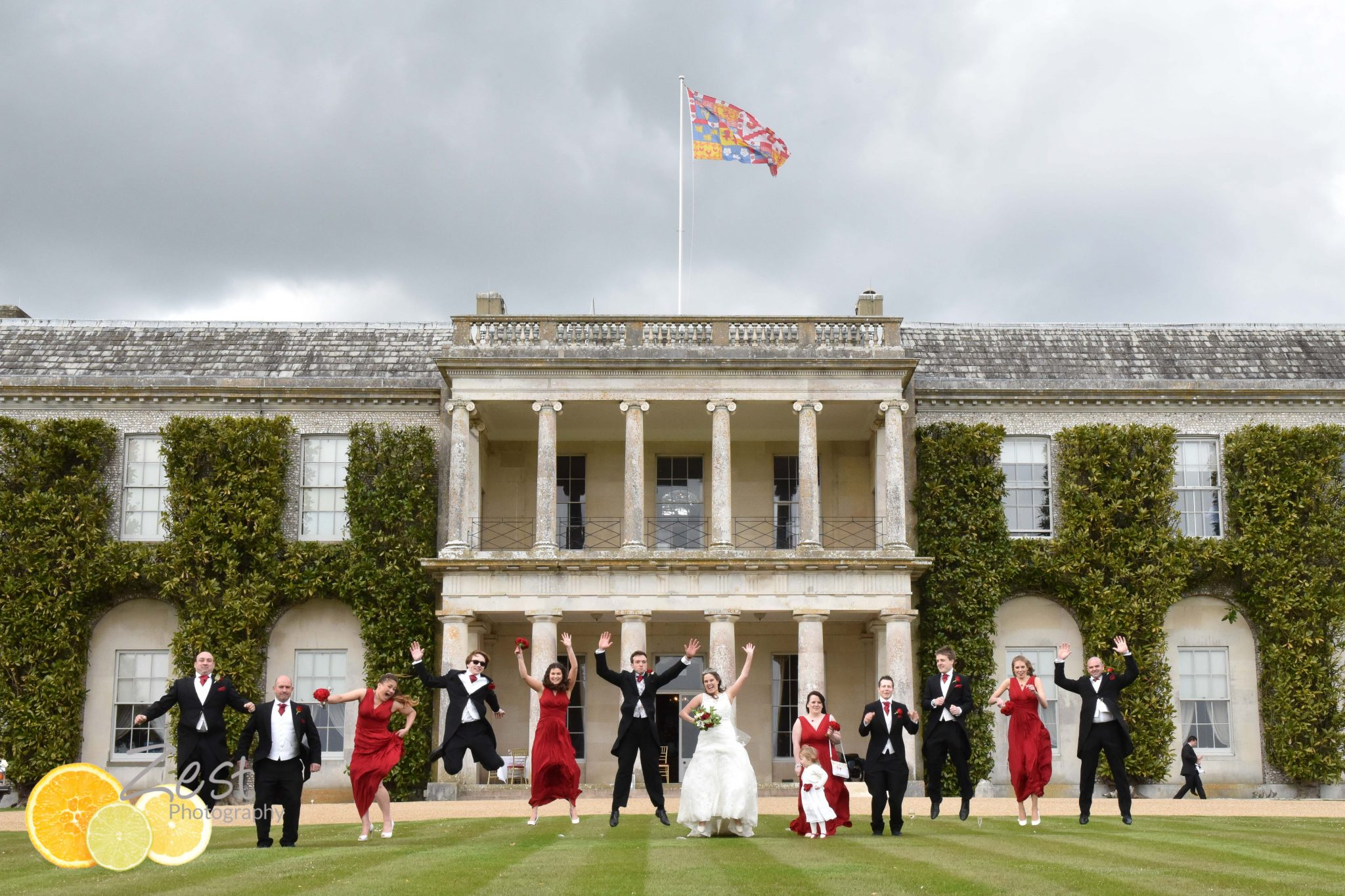 jumping wedding party outside goodwood house