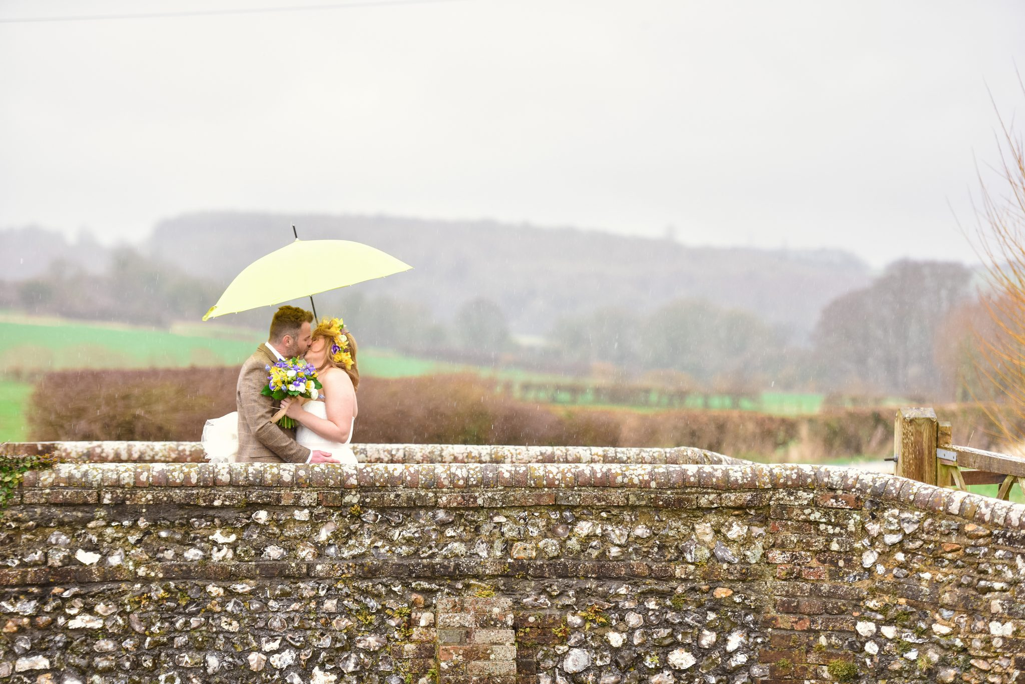 couple kissing on the bridge at farbridge bar taken by sussex wedding photographer zest
