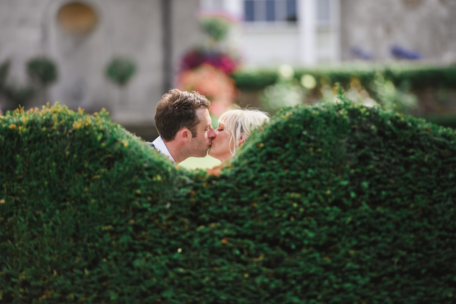 sussex wedding photographer zest photographs bride kissing groom behind a hedge