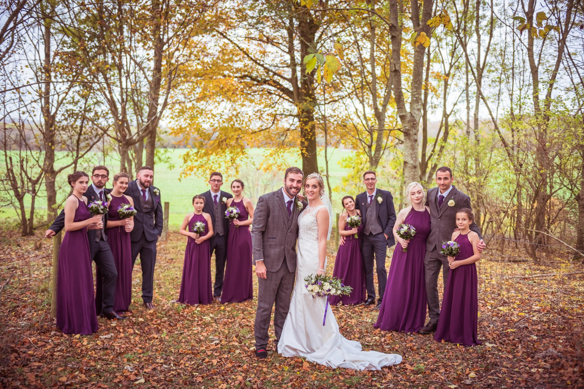 purple dresses and flowers in the autumn leaves by sussex photographer
