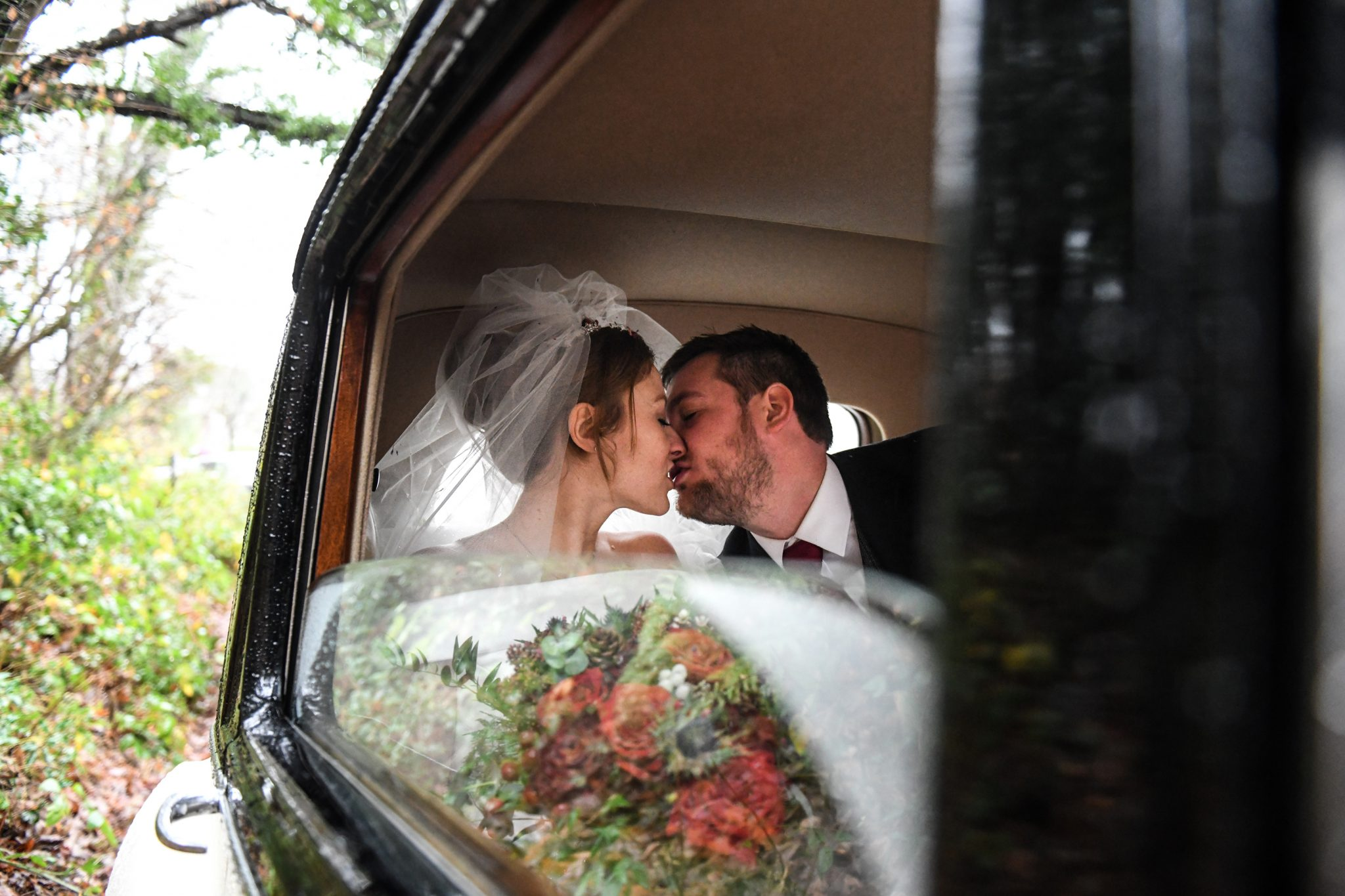 bride and groom kissing in a wedding car photographed by zest photography