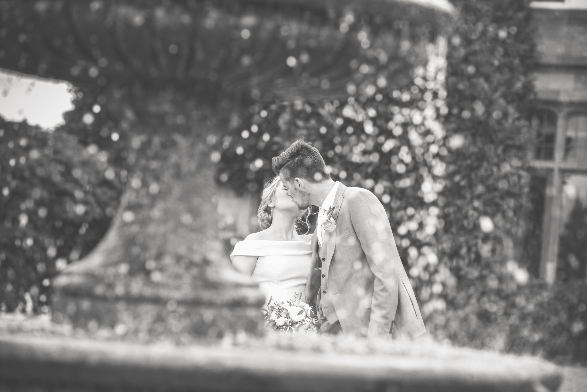 married couple kissing by fountain at cowdray house in sussex on their wedding day