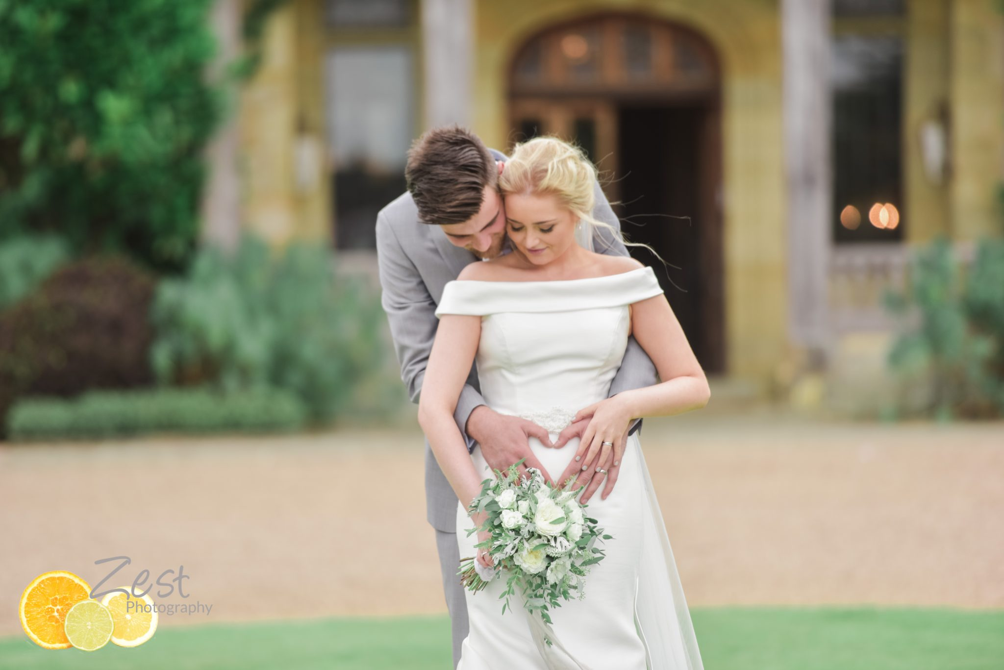 Groom embaces Bride infront of Cowdray House