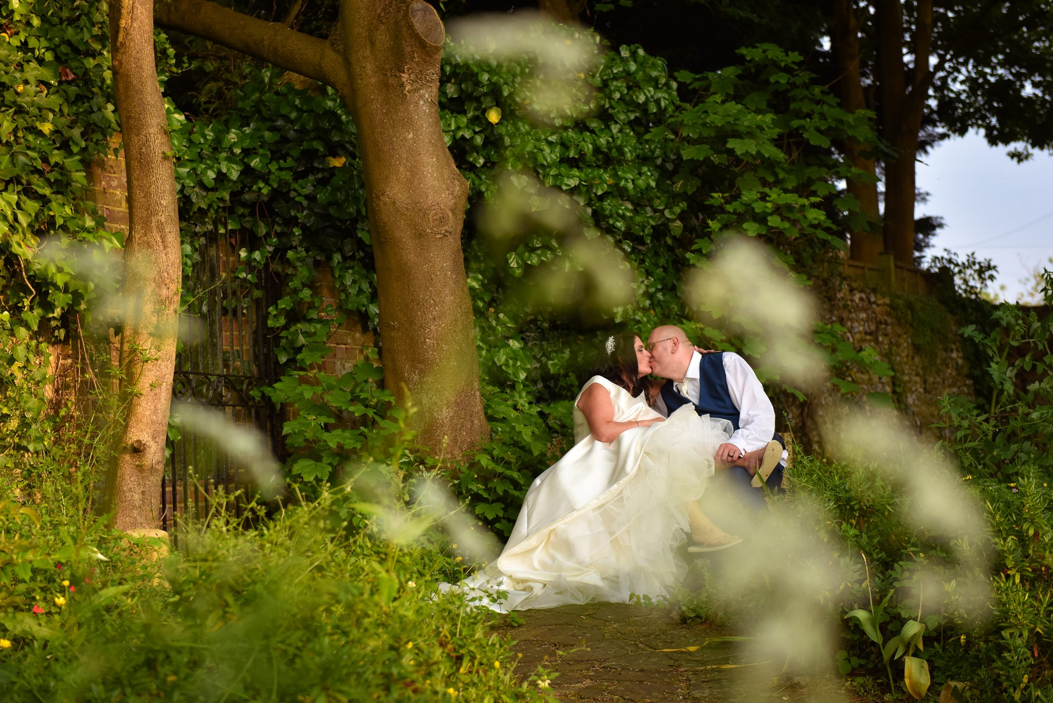 wedding couple sitting on a bench in sussex taken by west sussex photographer